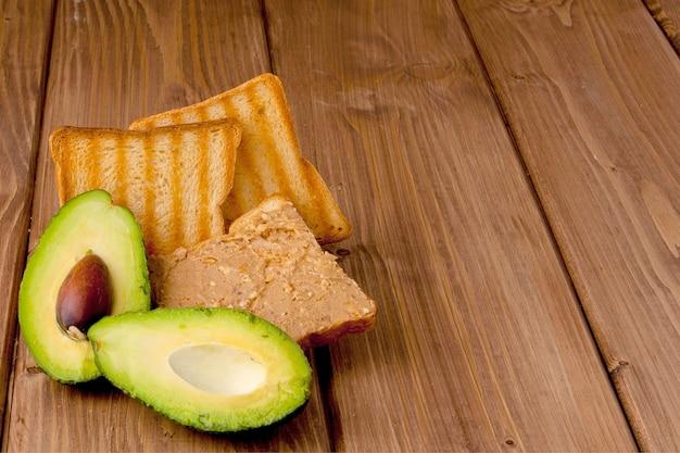 アボカドとトースター、木製の背景にピーナッツ ペースト