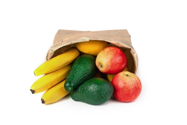 Авокадо, бананы и яблоки лежат в перевернутом пакете из крафт-бумаги на белом фоне.