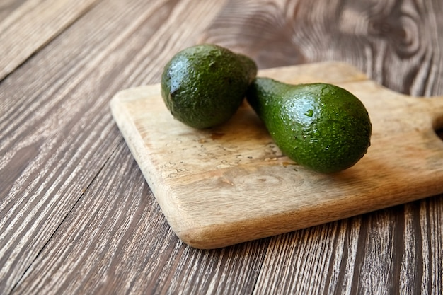 Avocados on cutting board on wooden table