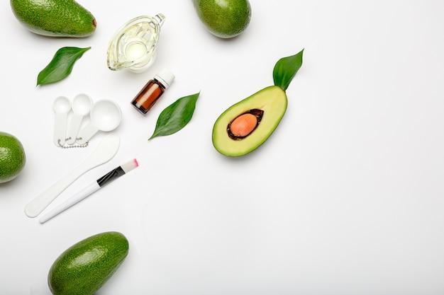 Авокадо листья шпатель кисти мерные ложки, эфирное масло на белом фоне