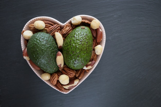 Avocados and nuts. two ripe avocados, pecans, brazil nuts and macadamia nuts in a heart shape dish