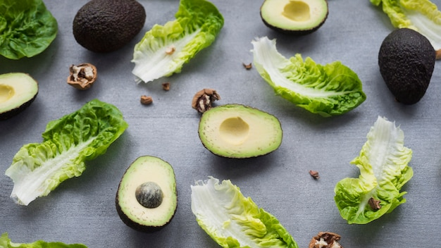 Avocados with lettuce scattered on table