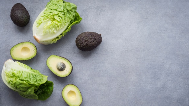 Avocados with lettuce on table