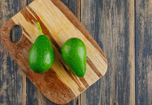 Avocados on wooden and cutting board. flat lay.