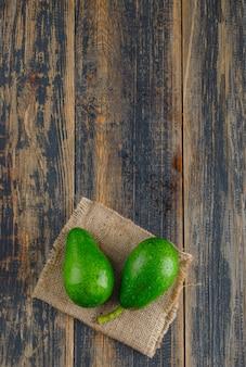Avocado su legno e pezzo di sacco. vista dall'alto.