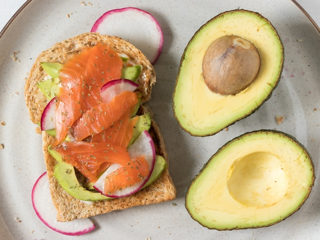 Avocadotoast with smoked salmon fish topping on a plate