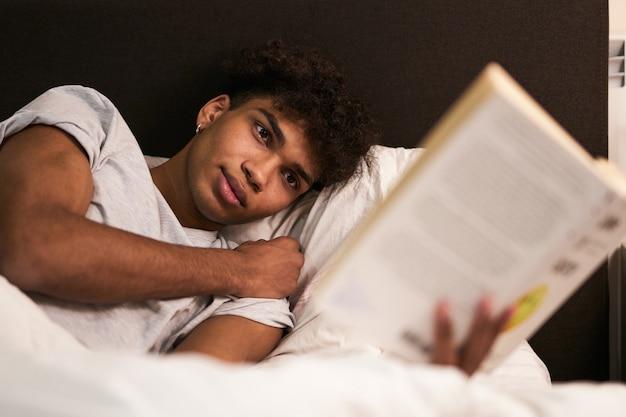 Избегайте гаджетов перед сном. портрет спокойного брюнетки, лежащего в постели дома, отдыхает и читает