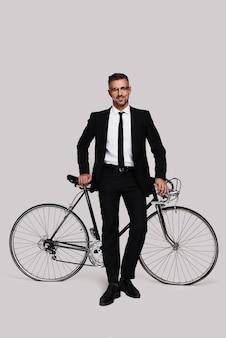 교통 체증 피하기. 그의 자전거에 기대어 회색 배경에 서있는 동안 웃고 전체 소송에서 좋은 찾고 젊은 남자의 전체 길이