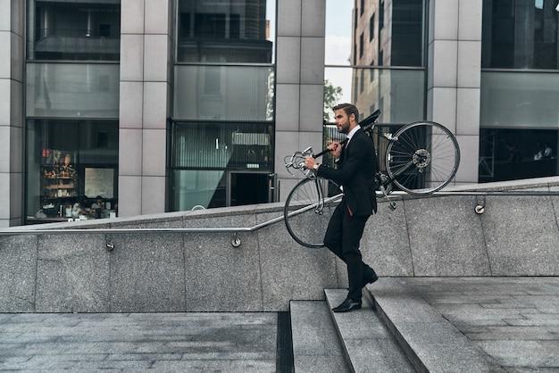 교통을 피합니다. 야외에서 걷는 동안 자전거를 들고 정장을 입은 젊은 남자의 전체 길이