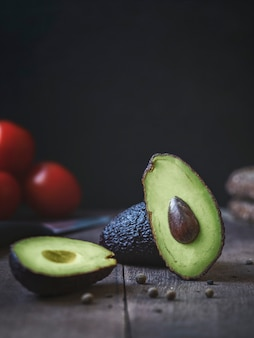 Avokado on the table, on the background tomatoes. high quality photo