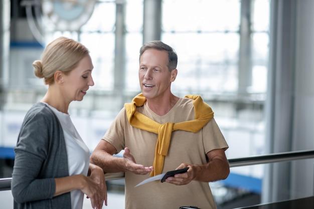出発を待っています。空港ターミナルの近くに立っている笑顔の女性のチケットとプロフィールを手で指しているパスポートを持つ格好良い男
