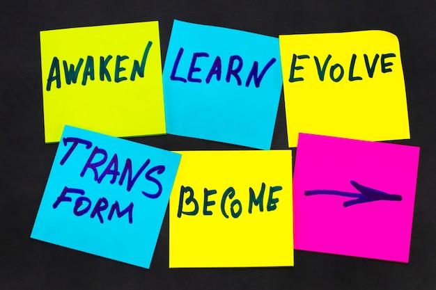 目覚め、学び、進化し、変容し、そして-インスピレーションを与える新年の目標や決議-黒板にカラフルな付箋紙。