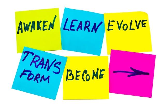 目覚め、学び、進化し、変容し、そして-インスピレーションを与える新年の目標や決議-白い背景にカラフルな付箋紙。