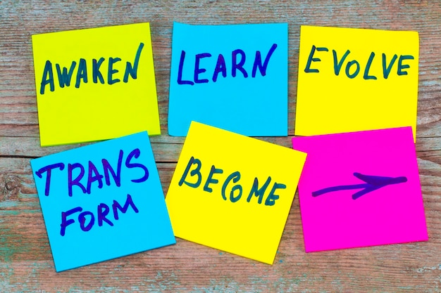 目覚め、学び、進化し、変容し、そして-インスピレーションを与える新年の目標や決議-木製の背景にカラフルな付箋紙。