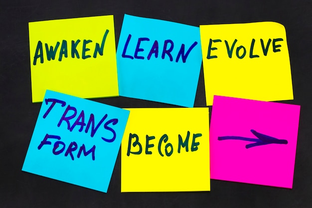 Awaken, learn, evolve, transform and become - inspirational new year goals or resolutions - colorful sticky notes on a blackboard.