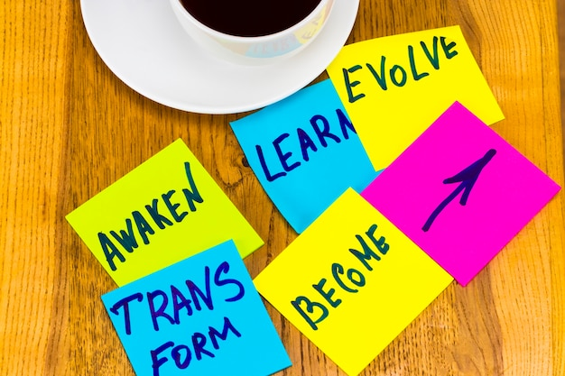 Awaken, learn, evolve, transform and become - inspirational new year goals or resolutions - colorful sticky notes on wooden background.