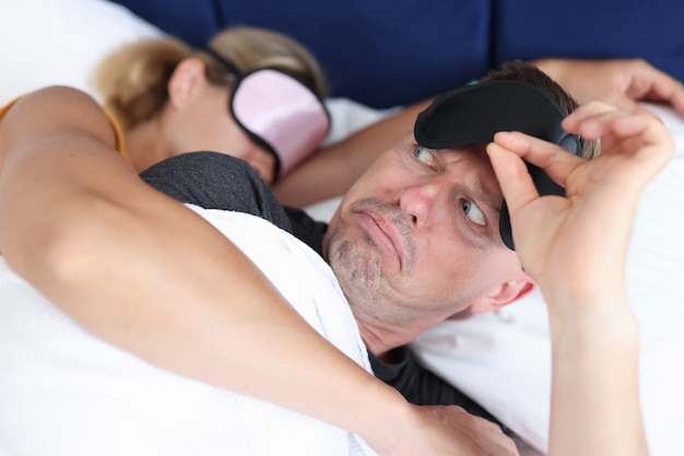 Awakened man looks at woman in dismay casual love relationship concept