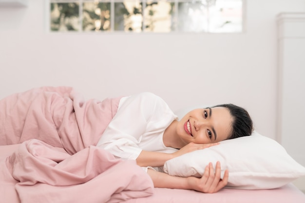 Awakening from sleep happy woman in bed and soft pillow blanket