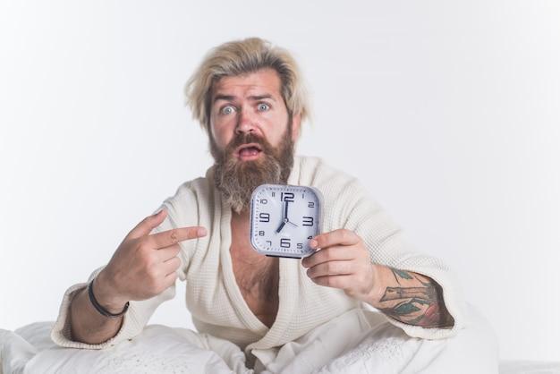 알람 시계와 함께 깨어있는 아침 남자 침대에서 수염 난 남자 아침 아침 일상적인 알람 시계 기상
