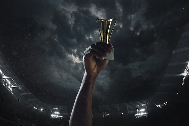 勝利の賞、曇った暗い空に対して勝者のカップを締める男性の手