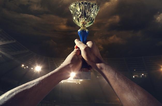 Награда за победу, мужские руки, сжимающие кубок победителей против пасмурного темного неба