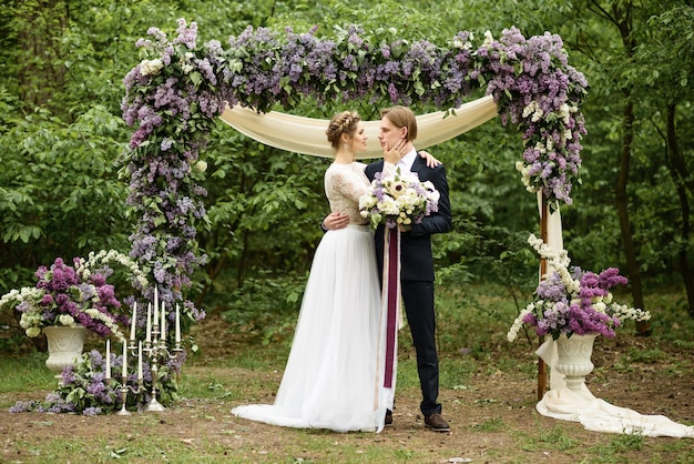 Away wedding ceremony in the woods. the bride and groom stand near the lilac flower arch