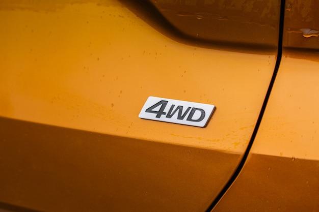 Эмблема полного привода на современной оранжевой детали автомобиля внедорожника крупным планом. хромированная эмблема all wheel drive.