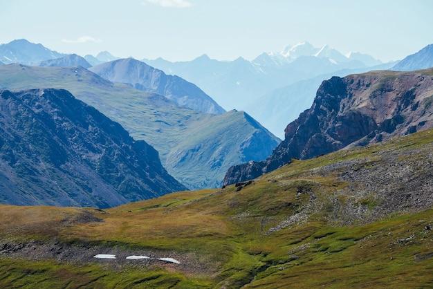 Потрясающий альпийский пейзаж с большой заснеженной горой за скалистыми горами и глубоким ущельем.
