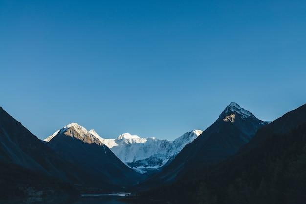 澄んだ青い空の下で金色の太陽の下で山のシルエットと雪に覆われた山の頂上を持つ素晴らしい高山の風景。影のある高原の谷にある美しい太陽に照らされた真っ白な山の壁と湖