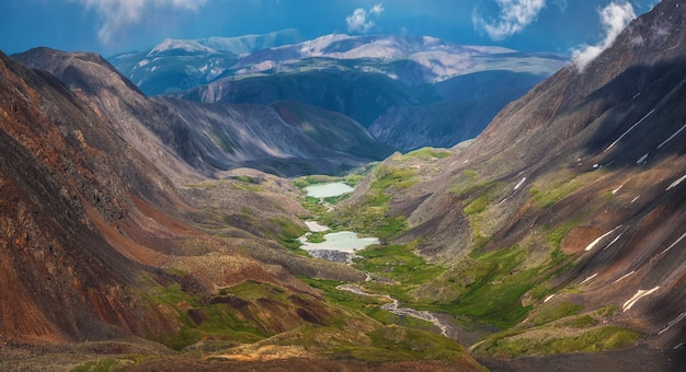 Awesome alpine panoramic view from pass to mountain valley in sunlight