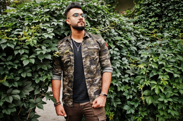 Awesome beautiful tall beard man in glasses and military jacket posed outdoor against arch of green leaves