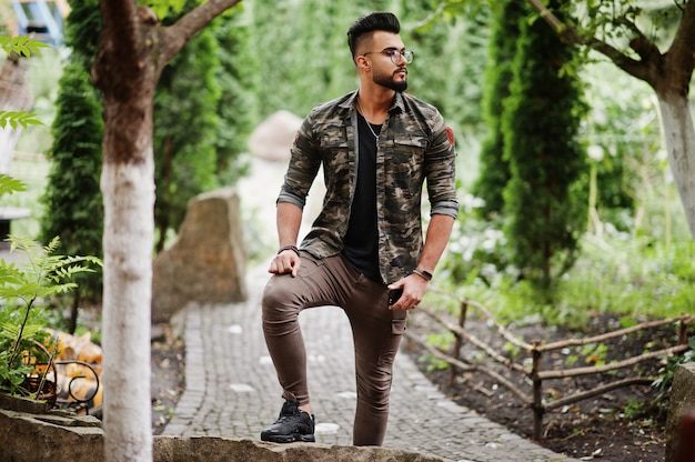 Awesome beautiful tall beard man in glasses and military jacket posed outdoor