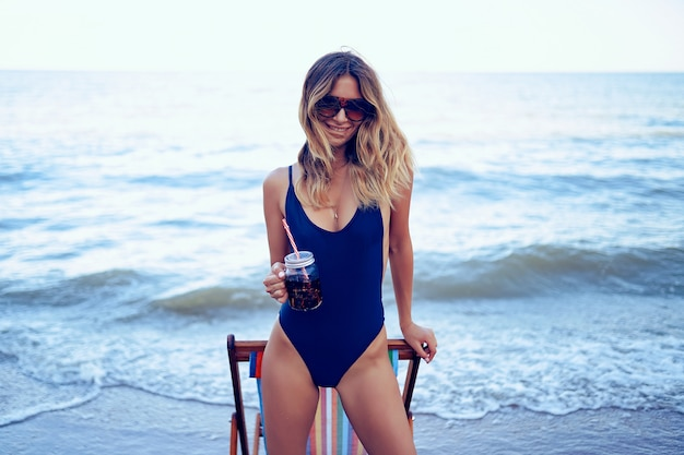 Awesome beauty blonde woman in sunglasses, swimsuit relaxing on beach and drinks coctail. summer vacation concept