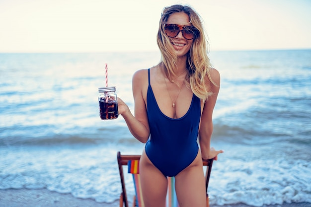 Awesome beauty blonde woman in sunglasses, swimsuit relaxing on beach and drinks coctail