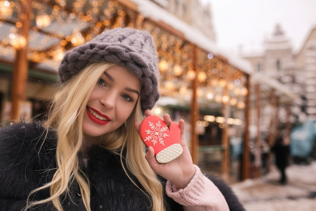 Awesome blonde woman holding savory gingerbread against light decoration at the christmas fair in kyiv