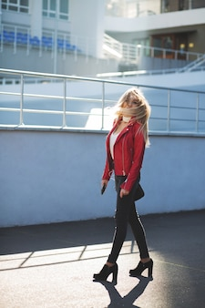 Awesome blonde woman wearing red jacket walking down the street with fluttering hair