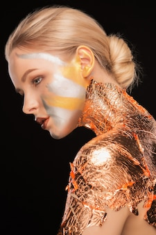 목과 등에 금박을 바르고 밝은 화장을 한 멋진 금발 여성
