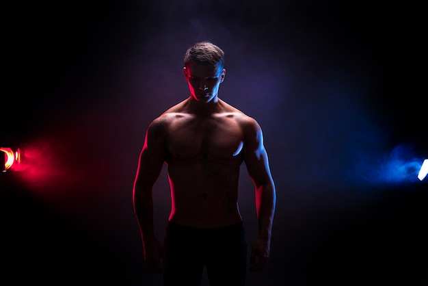 Awesome bodybuilder silhouette. handsome power athletic man bodybuilder. fitness muscular body on dark colour smoke scene. perfect male. tattoo, posing.