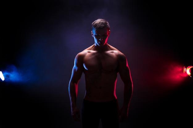 멋진 보디 실루엣. 잘 생긴 전원 운동 남자 보디입니다. 어두운 색 연기 배경에 피트니스 근육질 몸. 완벽한 남성. 문신, 포즈.