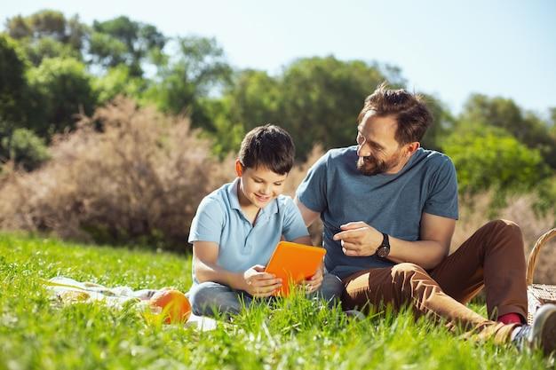 멋진 하루. 공원에서 아버지와 함께 앉아있는 동안 태블릿을 들고 매력적인 즐거운 소년