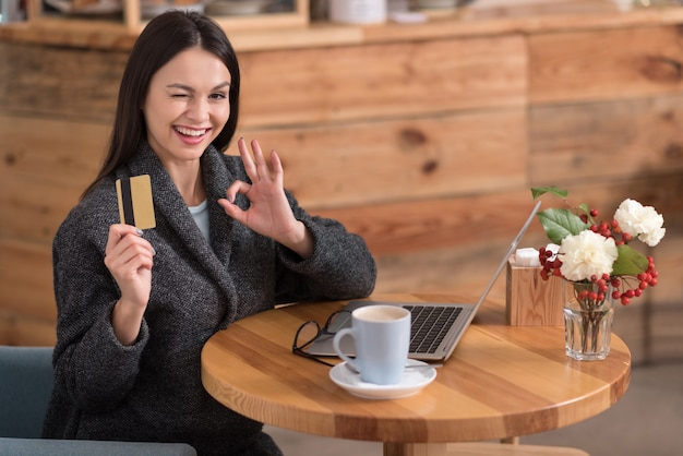 Отличные предложения. счастливая взволнованная красивая женщина улыбается и показывает дисконтную карту во время отдыха в кафе.