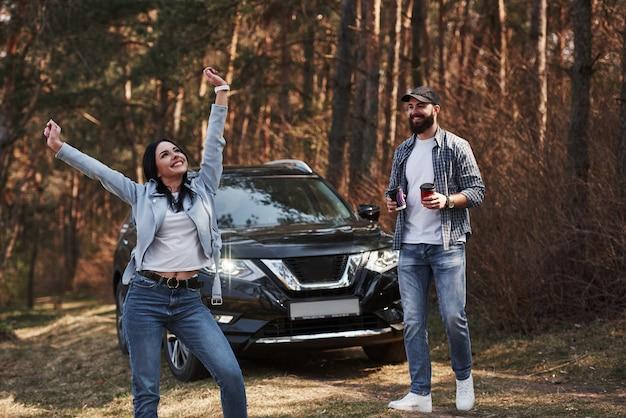 굉장한 감정. 자연을 즐기고 있습니다. 부부가 새 검은 차를 타고 숲에 도착했습니다.