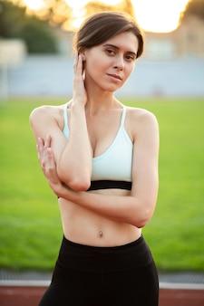 完璧なボディを持つ素晴らしいフィットネス女性は、草の近くでポーズをとるファッショナブルなスポーツウェアを着ています
