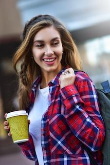 Потрясающая девушка в городском стиле гуляет по городу с кофе.