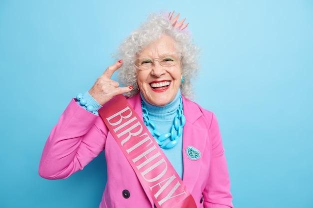 素晴らしい幸せな白髪の女性は、ロックンロールのジェスチャーをし、お祝いの服を着たクールな誕生日パーティーを楽しみ、笑顔で喜んで若返る