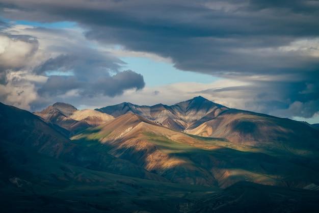 Потрясающий горный пейзаж с большими горами и голубым просветом в пасмурном небе в пасмурную погоду.