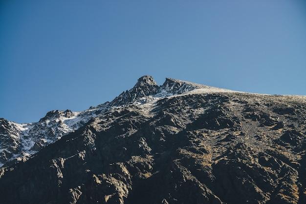 青い空の下で金色の日差しの中で白い雪と黒い峰の頂上を持つ素晴らしい山の風景。金色の日差しの中で美しい雪に覆われた先のとがったピーク。頂上が尖った雰囲気の山の風景。