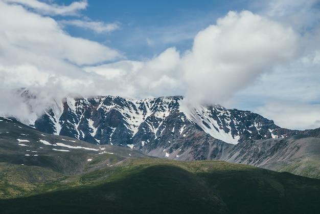 青い空の低い雲の中に大きな雪に覆われた山の尾根がある素晴らしい山の風景。太陽に照らされた緑の丘の上に雪が降る高い山脈のある大気の高原の風景。岩の美しい景色