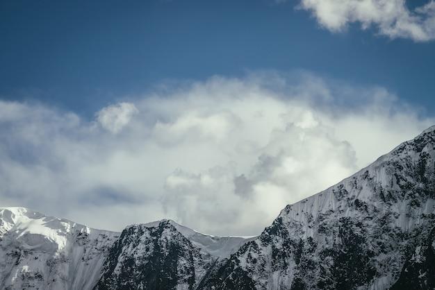 흐린 하늘 아래 검은 흰색 눈 덮인 산맥이 있는 멋진 산 풍경. 구름 아래 높은 산 벽이 있는 미니멀한 고원 풍경. 멋진 산등성이에 대한 최소한의 전망.