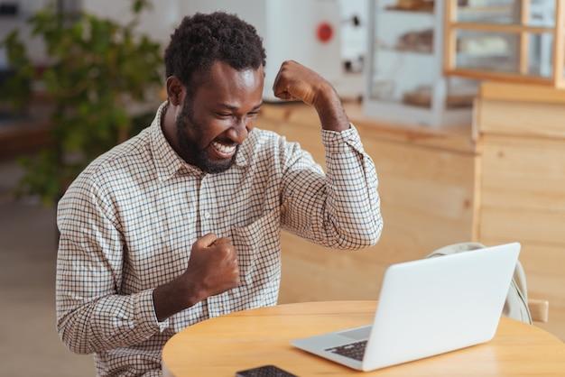 Отличные новости. веселый молодой человек сидит за столом в кофейне и поднимает руки на праздновании, радуется отличным новостям, прочитав электронную почту на ноутбуке